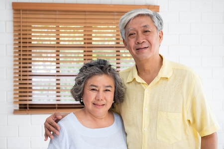 Asian senior couple embrace togerther and looking at camera in living room at home.Happy retirement lfie.aging at home concept Standard-Bild - 118844669