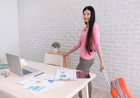Asian woman holding travel suitcase leaving from work on table and prepare to holiday vacation.out of office concept Standard-Bild - 118844670
