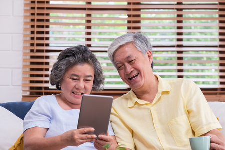Asian senior couple learn to using table compute on sofa in living room at home.senior with technology lfiestyle.aging at home concept Standard-Bild - 118844674