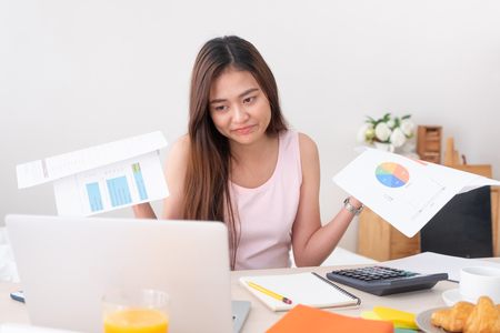 Asian woman freelancer upset with work problem with laptop on mess table.work at home concept.stress working Standard-Bild - 118844699