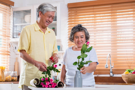 Asian Senior couple husband and wife flower arrangement to vase on table in kitchen at home in Valentine's Day.lovely senior couple concept Standard-Bild - 118844700