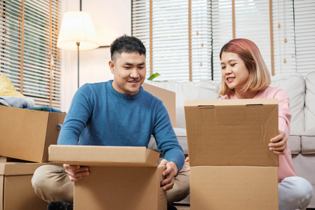 Happy asian couple open cardboard boxes  while moving to new home at sofa in living room.unpacking for new house Standard-Bild - 118844703