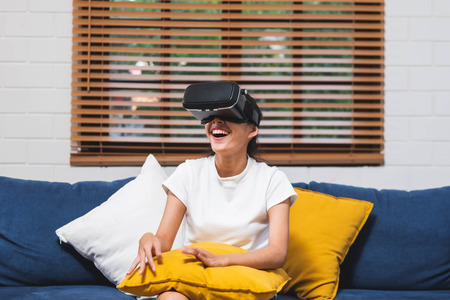 Asian woman wear vr headset glasses and play virtural reality  sitting on sofa at home.digital tehcnology lifestyle. Standard-Bild - 118844081