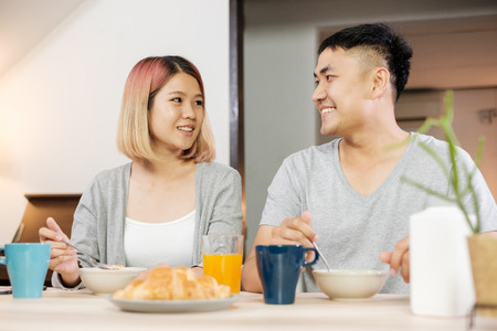 happy asian couple in pajamas sitting at table in kitchen at home in morning and having cereal breakfast together Standard-Bild - 118844087