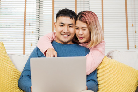 Asian couple watching video live on laptp on sofa in living room at home.lover spending time together.wife embrace husband from back Standard-Bild - 118844089