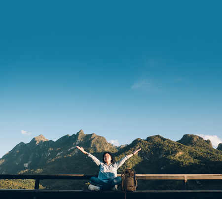 Asian woman traveler  sitting and arms up in the air at view point terrace at landscape view of mountain with cloud and blue sky in sunny day at forest.backpacker explore nature life Standard-Bild - 118844091