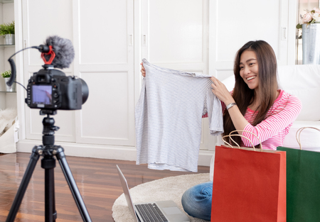 Asian young female blogger recording vlog video with review cloths T-shirt at home online influencer on social media concept.live streaming viral. Standard-Bild - 118844095