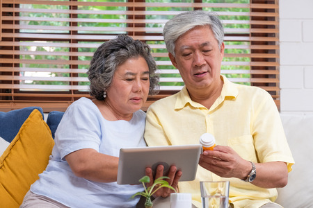 Asian senior couple use tablet searching prescription of pill while sitting on sofa at home,senior learn to use technology.aging at home. Standard-Bild - 118844150
