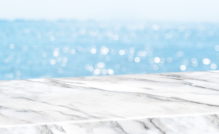 Empty glossy white marble table top with blur sky and sea boekh background,banner mock up template for display of product Standard-Bild - 118844654