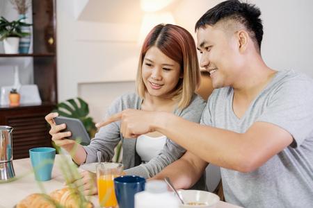 キッチンのテーブルに座って、朝自宅でモバイルトーガーでビデオを見て、シリアルの朝食を持っているパジャマで幸せなアジアのカップル。