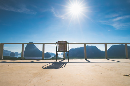 Chair on terrace at panoramic sea view with sun and blue sky.tropical climate view. Standard-Bild - 120919660