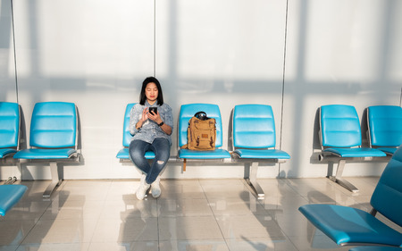 Asian woman using mobile kill time when waiting for departure at airport terminal.travel concept Standard-Bild - 120919671