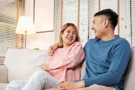 Asian couple embracing and laughing while sitting at sofa in house.lover couple in home concept Standard-Bild - 120919674