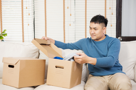 asian man open cardboard boxes  while moving to new home at sofa in living room.unpacking for new house Standard-Bild - 120919936