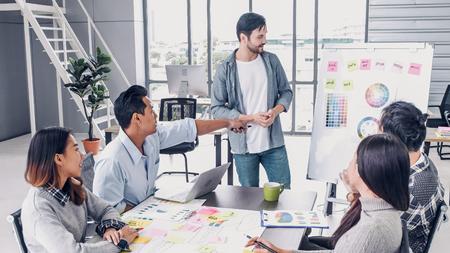 Man Creative Director 팀은 디자이너 팀과 함께 브레인스트롬 브랜딩 프로젝트를 이끌고 회의 테이블에서 좋은 아이디어에 대해 엄지손가락을 치켜듭니다. 크리에이티브 사무실의 토론 아이디어 스톡 콘텐츠