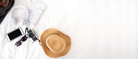 Sommerreiseartikel auf der Decke auf dem Bett. Draufsicht auf das Reisezubehör (Kamera, Hut, Kopfhörer, Karte) auf der Bettdecke. Vorbereitung auf die Urlaubsreise. Reiseplanung. Banner für die Anzeige des Designs