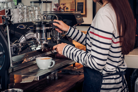 Asian barista woman making coffee cappuccino at cafe with machine at counter bar in eatery,Food and drink service concept. Stock Photo