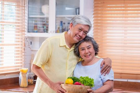 Portret szczęścia asian starszy para w kuchni z miską świeżej sałatki i patrząc na kamery, starzenie się w domu conept. Zdjęcie Seryjne