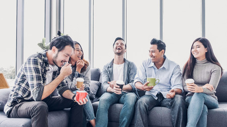 creatieve ontwerper neemt koffiepauze in kantoorcafetaria. multi-etnisch medewerker zit op de bank en praat en veel plezier Stockfoto