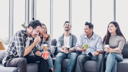 Kreative Designer machen Kaffeepause in der Cafeteria des Büros. multiethnischer Mitarbeiter sitzt am Sofa und redet und hat Spaß Standard-Bild