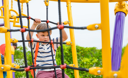 jongen die plezier heeft om te spelen op klimspeelgoed voor kinderen op schoolplein, terug naar schoolactiviteit. kleuterschool voorschoolse