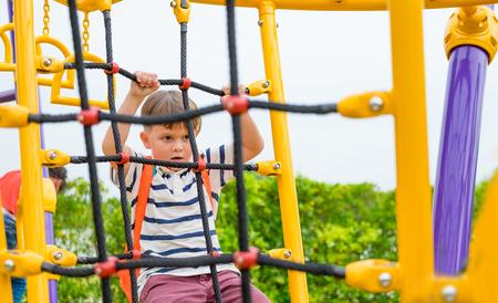 Kinderjunge, der Spaß hat, auf dem Kinderkletterspielzeug auf dem Schulhof zu spielen, zurück zur Schulaktivität. Kindergarten Vorschule