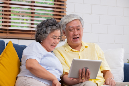 happy Asian senior couple use tablet video chatting to family at home.aging at home concept
