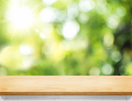 Dessus de table en planche de bois vide avec arbre flou dans le parc avec lumière bokeh en arrière-plan, modèle de maquette pour l'affichage de votre conception, bannière pour la publicité du produit Banque d'images