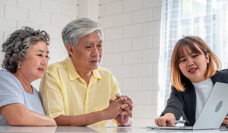 Asian senior couple with financial advisor about tax and retirement document at home.happy aging at home concept.