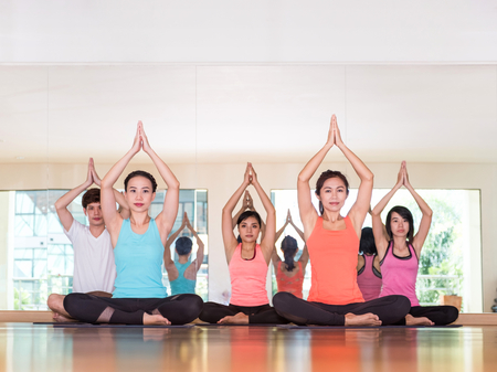 Yoga class in studio room,Group of people doing namaste pose with clam relax emotion,Meditation pose,Wellness and Healthy Lifestyle