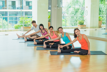 Yoga class in studio room,Group of people doing seated side stretch right poses with calm relax emotion,streaching pose,Wellness and Healthy Lifestyle. Stock Photo