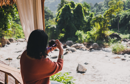 Woman photographer take a picture of steam water,Travel wanderlust concept.