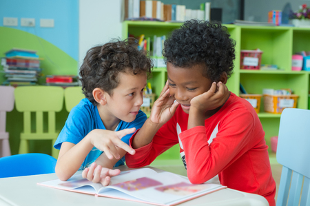 Two boy kid sit on table and coloring in book  in preschool library,Kindergarten school education concept.
