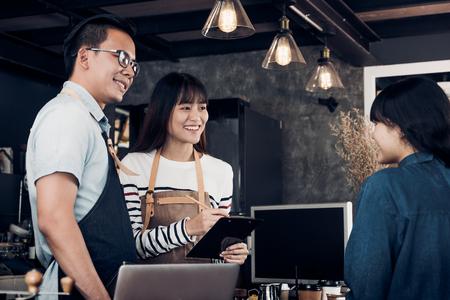El camarero y la camarera del barista de Asia toman el pedido del cliente en la cafetería, el propietario de dos cafés escribe el pedido de bebidas en el mostrador, el concepto de negocio de alimentos y bebidas, el concepto de mente de servicio. Foto de archivo