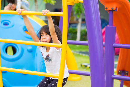 asia kid girl having fun to play on childrens climbing toy at school playground,back to school outdoor activity.