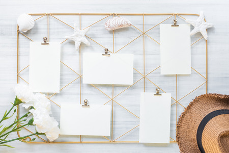 Top view set of note pad clip frame and summer hat with flower on white wood table.summer vacation background Фото со стока