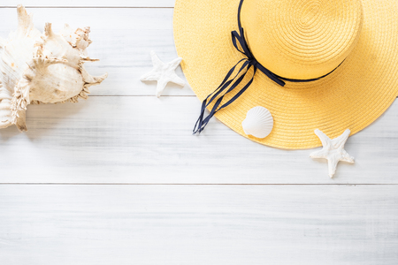 top view of summer yellow female hat with sunglasses and shell and star fish decoration on white wood table.summer vacation Zdjęcie Seryjne