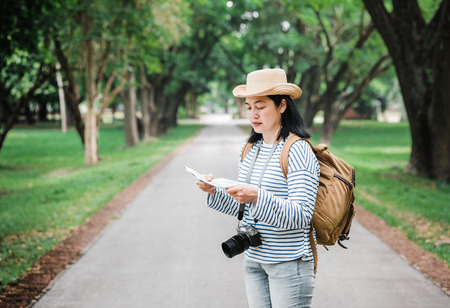 Asian woman backpack traveler use map when traveling at rain forest.Holiday vacation concept.journey lifestyle.solo travel. 版權商用圖片