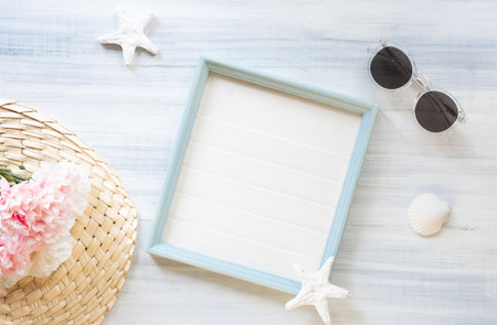 top view of summer blue picture frame with sunglasses and seashell and star fish and pink flower decoration on white wood table.summer vacation