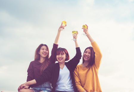 Happy group of asian girl friends enjoy laughing and cheerful sparkling wine glass at rooftop party,Holiday celebration festive,teeage lifestyle,freedom and fun. Banco de Imagens - 124604194
