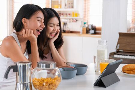 Happy asian lesbian woman couple video chat with friend in breakfast time at house in morning with love and tender.LGBTQ lifestyle concept