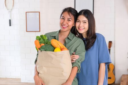 Happy asian couple lesbian holding vegetable bag  looing at camera after shopping at grocery store at home.LGBTQ lifestyle concept