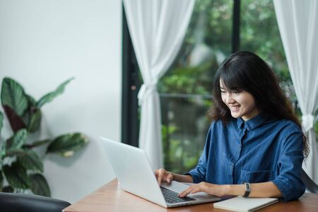 Asian woman using on laptop computer near window at cafe restaurant,Digital age lifestyle,using Technolgy concept,co working space Stock Photo
