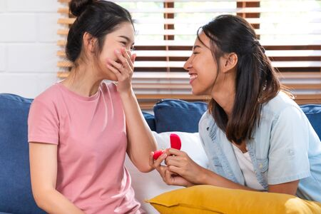 Happy asian couple lesbian proposal with ring for marry at living room at home.LGBTQ lifestyle concept