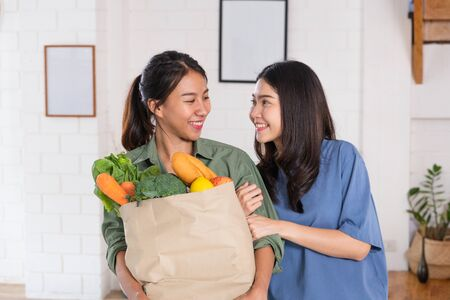 Happy asian couple holding vegetable bag after shopping at grocery store at home.LGBTQ lifestyle concept