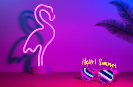 Hello summer with flamingo,palm leaf,sunglasses refection neon pink and blue and green light on table with copy space.Trendy vacation holiday background