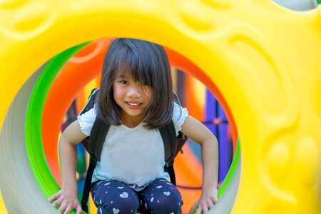 asian kid girl having fun to play on children's climbing toy at school playground,back to school outdoor activity.