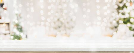 Empty white wold table top with abstract warm living room decor with christmas tree string light blur background with snow,Holiday backdrop,Mock up banner for display of advertise product Imagens