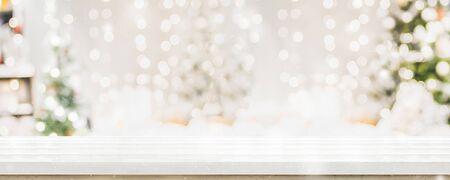Leere weiße Wold-Tischplatte mit abstraktem, warmem Wohnzimmerdekor mit Weihnachtsbaumschnurlichtunschärfehintergrund mit Schnee, Feiertagshintergrund, Mock-up-Banner für die Anzeige von Werbeprodukten