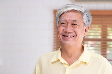 Asiatischer älterer Mann lächelt im Wohnzimmer zu Hause, glückliches Altern zu Hause Konzept.